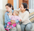Mature woman comforting adult daughter with toddler women at home Stock Image