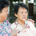 Mature woman consoling her crying old mother asian women at outdoor natural green park Royalty Free Stock Photos