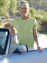 Mature woman by convertible car smiling portrait Royalty Free Stock Photography