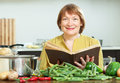 Mature woman cooking with cookery book in kitchen smiling vegetarian lunch Royalty Free Stock Photos
