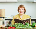 Mature woman cooking with cookery book vegetarian lunch in domestic kitchen Royalty Free Stock Photo