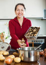 Mature woman cooking soup with dried mushrooms smiling in kitchen Royalty Free Stock Image