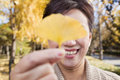 Mature woman covering her eyes with yellow ginkgo leaf Royalty Free Stock Image