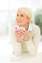 Mature woman cup coffee thoughtful holding of Stock Images
