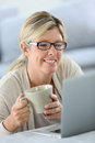 Mature woman with cup of coffee working on laptop eyeglasses websurfing Royalty Free Stock Photos