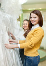 Mature woman with daughter chooses white gown women at shop of wedding fashion Royalty Free Stock Photos