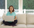 Mature woman displaying smile while using computer at home looking forward sitting on her white couch her laptop in her family Royalty Free Stock Photography