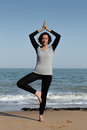 Mature woman doing yoga tree pose on the beach or vrksasana with hands above head Royalty Free Stock Image