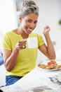 Mature woman eating breakfast and reading newspaper holding hot drink smiling at camera Royalty Free Stock Photos
