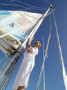Mature woman erecting sail on boat smiling portrait low angle view Royalty Free Stock Photography