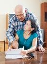 Mature woman fills documents man helping her serious women senior men at home Stock Image
