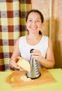Mature woman grating cheese Stock Image