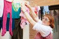 Mature woman hanging clothes to dry on clothes line after laundry Stock Images