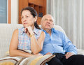 Mature woman having conflict with her senior husband women in living room at home Royalty Free Stock Photo