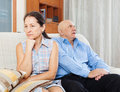 Mature woman having conflict with senior husband women her in living room Royalty Free Stock Photos