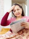 Mature woman having grief after readed news in newspaper Royalty Free Stock Images