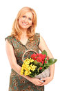 Mature woman holding a basket full of flowers Royalty Free Stock Image