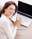 Mature woman holding coffee cup in front of laptop Royalty Free Stock Images