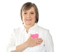 Mature woman holding her paper heart close to body Royalty Free Stock Photos