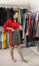Mature woman holding Mini Skirt in Closet Stock Photography