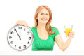 Mature woman holding a wall clock and glass of orange juice on table isolated on white background Stock Photos