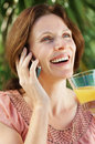 Mature woman with juice glass talking on the phone Royalty Free Stock Photography