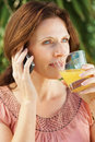 Mature woman with juice glass talking on the phone Stock Images