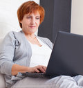 Mature woman with laptop female computer at home Royalty Free Stock Images