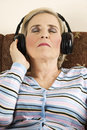 Mature woman listeni music in headphones Royalty Free Stock Image