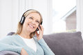 Mature Woman Listening To Music On Wireless Headphones Royalty Free Stock Photo