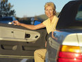 Mature woman with mobile phone in car door open portrait Stock Photos