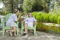 Mature woman and mother relaxing with man and child fishing in the background women men Stock Photo