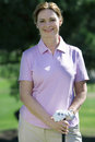 Mature woman, in pink polo shirt and golf glove, standing on golf course, leaning on golf club, smiling, front view, portrait Royalty Free Stock Photo