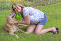 Mature woman playing with her dog. Royalty Free Stock Images