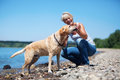 Mature woman plays with a dog at the river