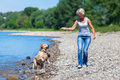 Mature woman plays with a dog at riverbanks Royalty Free Stock Photo