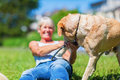 Mature woman plays with her dog outdoors Royalty Free Stock Photo