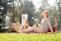 Mature woman posing in park with her husband women a lying on lap and reading a newspaper on a beautiful sunny day Royalty Free Stock Image