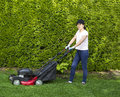 Mature woman preparing to work on grass yard horizontal photo of a use an old gas lawnmower with tall bushes and flower garden in Royalty Free Stock Image