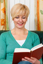 Mature woman is reading a book Royalty Free Stock Photo