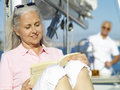Mature woman reading book on boat man in background women men Stock Photography