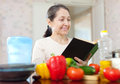 Mature woman reads cookbook in the kitchen Royalty Free Stock Photos