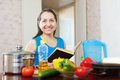 Mature woman reads cookbook in the kitchen at home Royalty Free Stock Photos