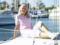 Mature woman reclining on deck of boat smiling portrait Stock Image