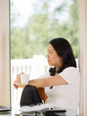 Mature woman relaxing while drinking coffee at home vertical image of working from with blurred out daylight coming in from window Stock Images