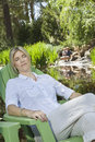 Mature woman resting in chair with man and son fishing in the background women men Royalty Free Stock Images