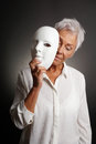 Mature woman revaling sad face behind mask Royalty Free Stock Photo
