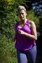 Mature woman running on a run outdoors Stock Photos