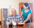 Mature woman serving toast to happy husband women senior in morning Stock Photos