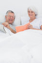 Mature woman showing her book to husband women in bed Royalty Free Stock Images